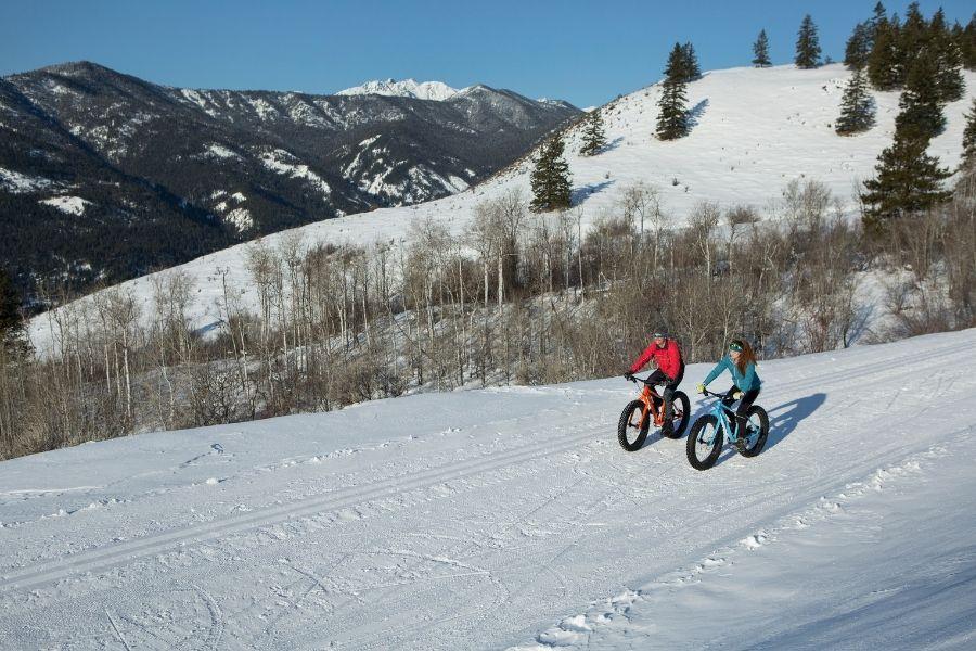 Two people ride fat bikes in winter