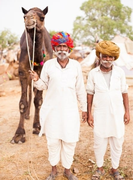 Two men walk with a camel during the Pushkar Camel Fair in India