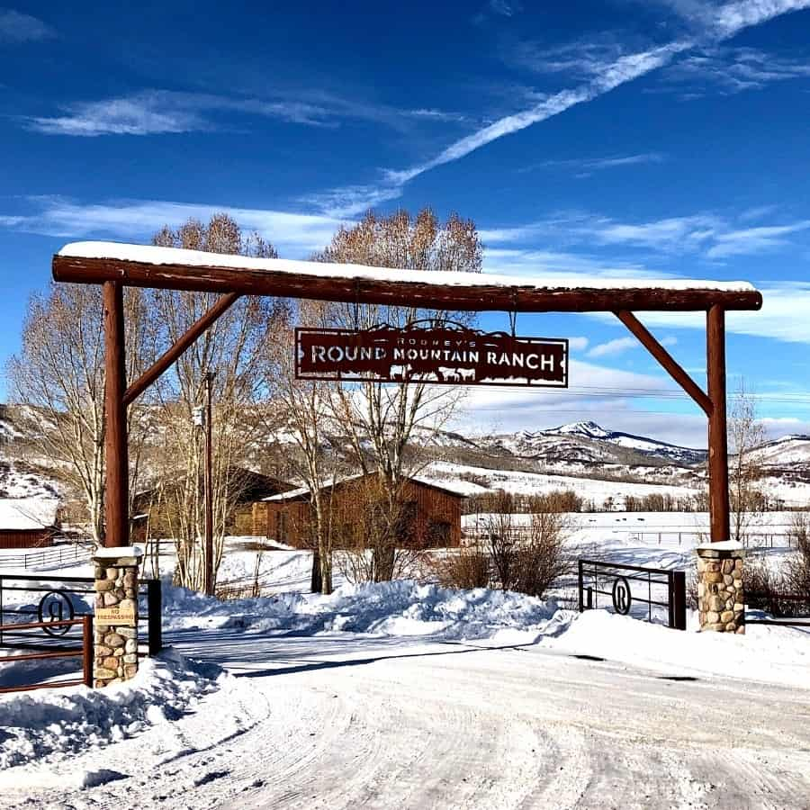 A ranch gate with blue skies and mountains beyond, in northern Colorado