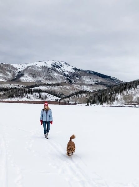 A woman hiking with her dog at Pearl Lake State Park in winter