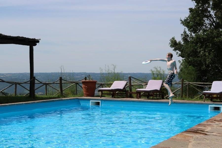 A boy plays frisbee at the swimming pool at the Umbria Agriturismo, Antica Olivaia