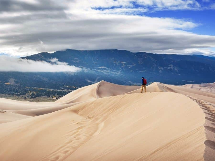 A man walks across a dune at Great Sand Dunes National Park in spring