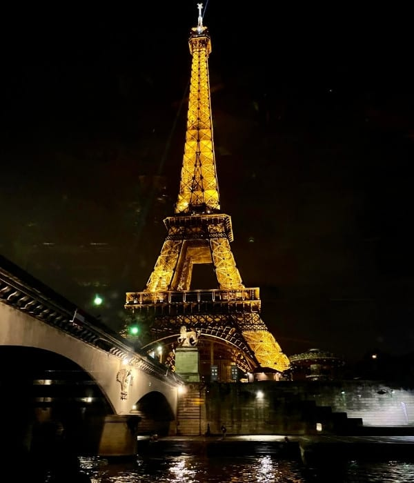 A view of the Eiffel Tower from the Seine River in Paris at night