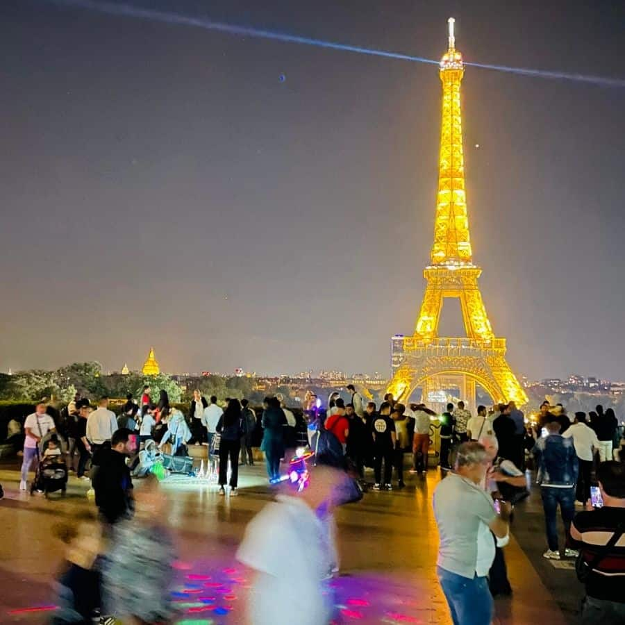 A view of the Eiffel Tower from the Trocadero in Paris with lots of people, lights and activity happening