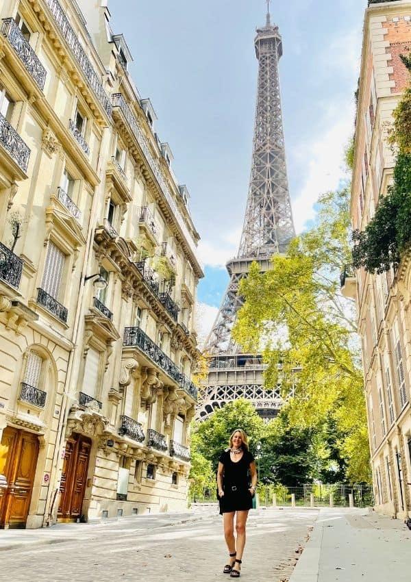Susan Heinrich stands in front of the Eiffel Tower on the rue de l'universite Paris