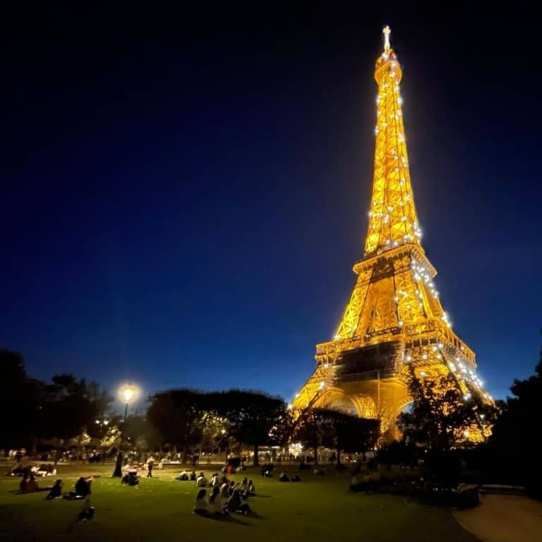 A gorgeous night time view of the Eiffel Tower from the Champ de Mars park in Paris. Visitors are spread out on the lawn in front of the tower