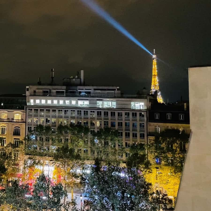 The Champs Elysees at night and an Eiffel Tower view in the distance