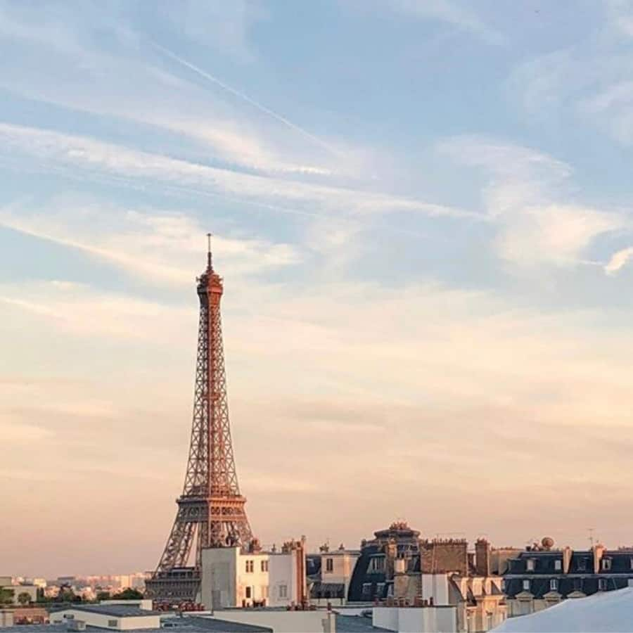 view of the eiffel tower among the rooftops, from the peninsula hotel paris