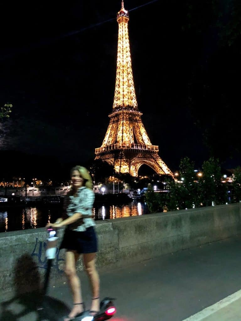 Susan Heinrich riding a scooter past the Eiffel Tower at night