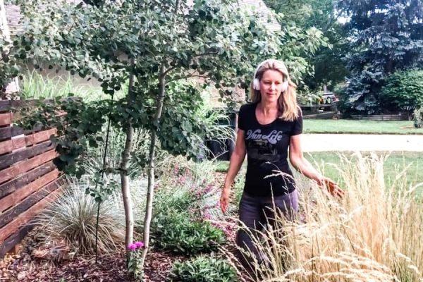 Susan Heinrich walking through a garden with headphones on