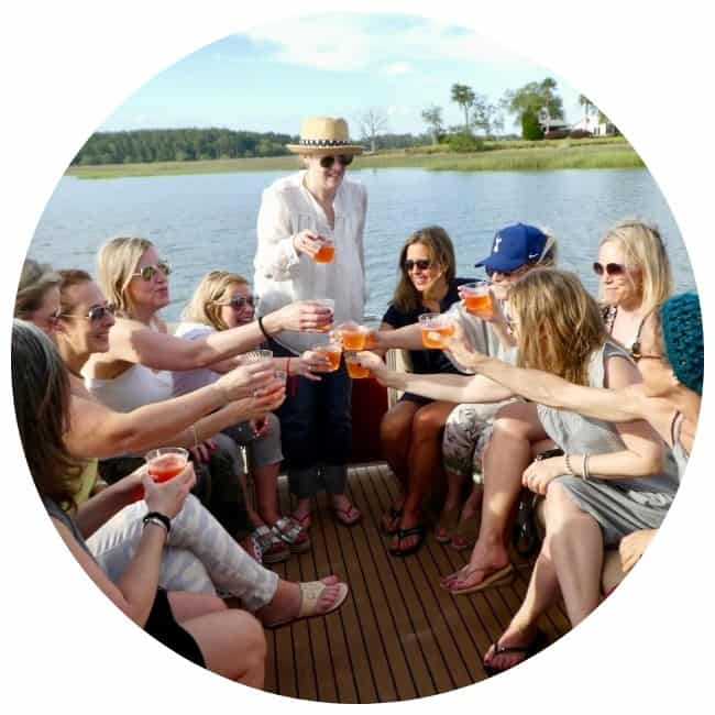 A group of women toast one another on a boat celebrating a 50th birthday