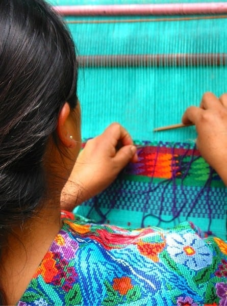 A Guatemalan woman does traditional weaving