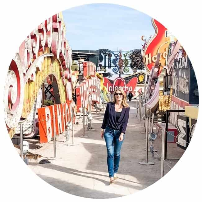 A midlife woman walks past bright vintage signs at the Neon Museum in Las Vegas