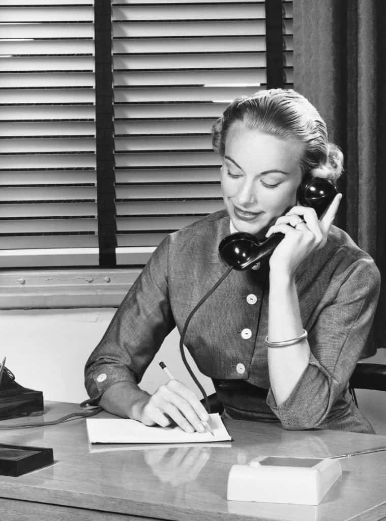 A black and white photo of a woman answering an old-fashioned phone