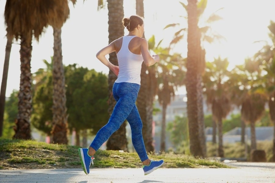 A midlife woman runs on a path lined with palm trees