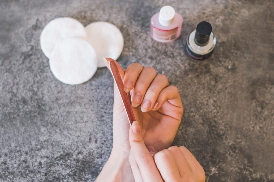 A woman gives herself a manicure