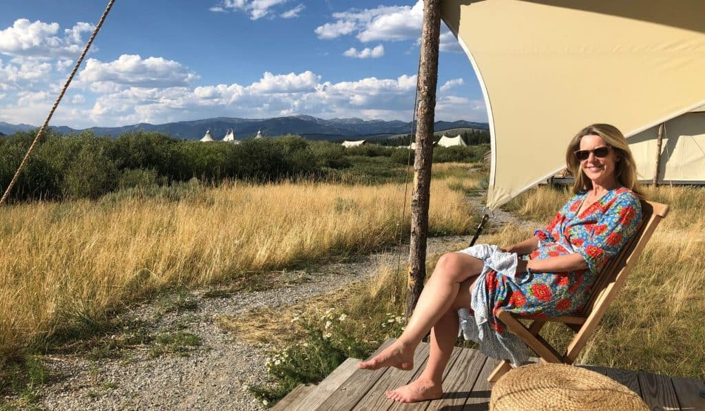 midlife woman sits in glamping tent in Montana