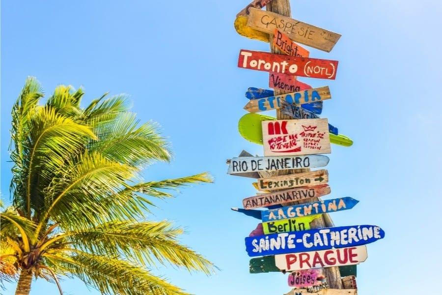 A signpost with names of cities stacked on it