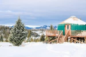 A yurt with mountains beyond at Pearl Lake Colorado in winter