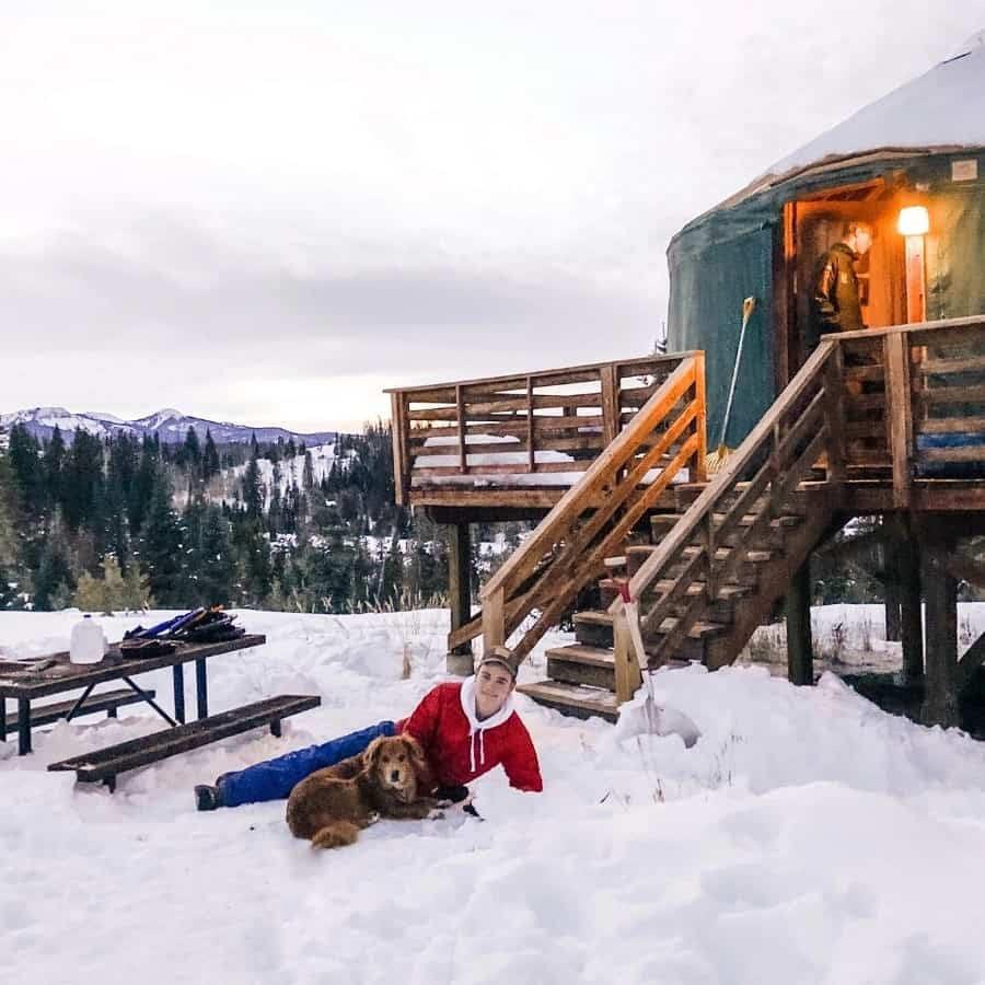 A young man and dog lay in the snow outside a yurt at Pearl Lake State Park