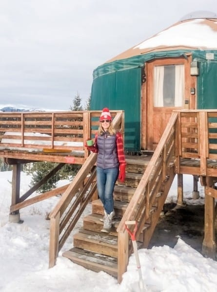 A woman stands on the steps of a yurt surrounded by snow