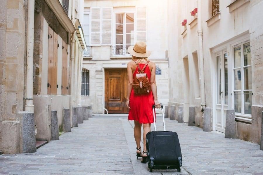A woman pulls a carry-on bag down a cobblestone laneway