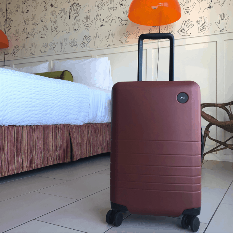 A Monos carry-on bag in a pretty hotel room in Los Angeles
