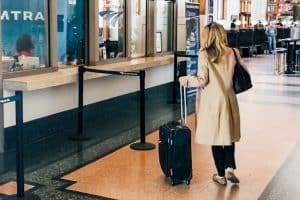 A woman walks through a train station with carry-on luggage