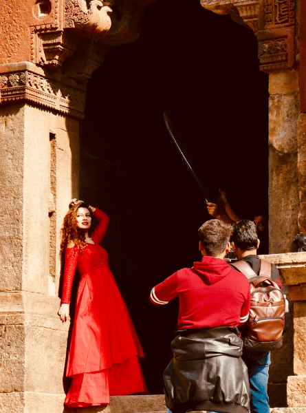 A woman poses in a red dress at a photo shoot at the Lodi Tomb in Delhi