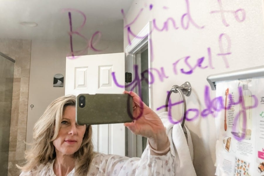 """A woman faces a mirror with the words Be Kind to Yourself Today"""""""
