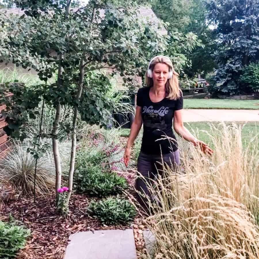 "Susan Heinrich walks through a garden with white ""beats"" headphones on"
