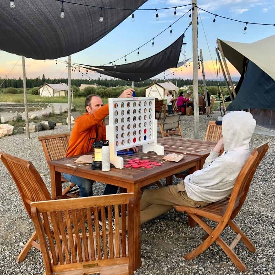 A father and son plan Connect Four at a table at Under Canvas Yellowstone
