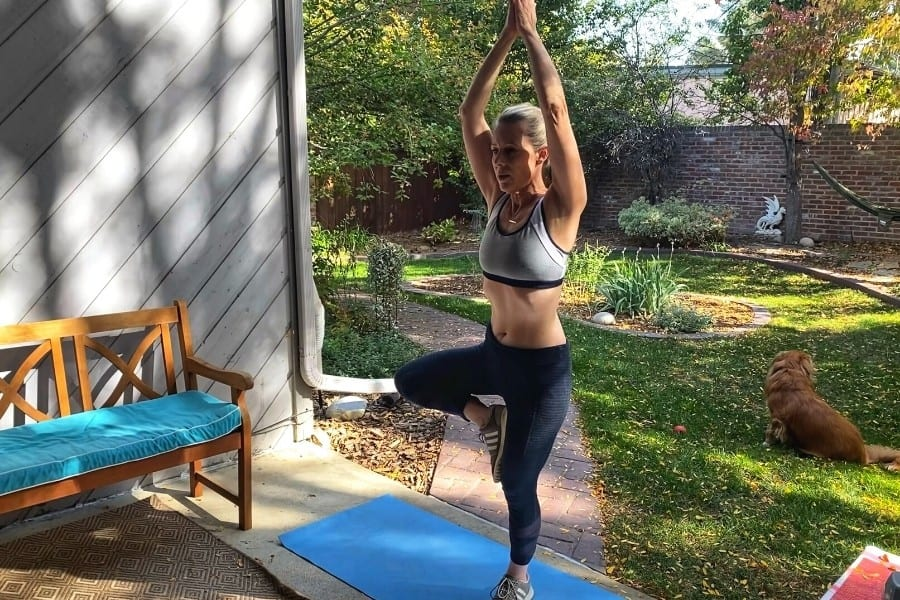 Susan Heinrich does a yoga tree pose in her backyard