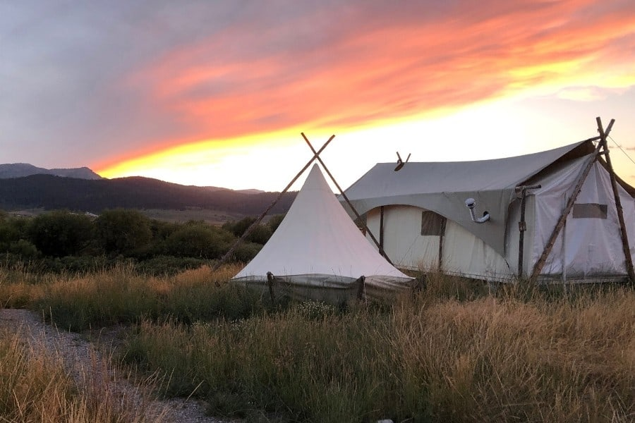 A white glamping tent and tipi are set in a mountain meadow with the sun setting beyond