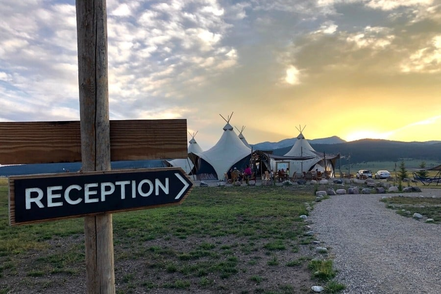 A reception sign points down a path toward a group of glamping tents at Under Canvas Yellowstone