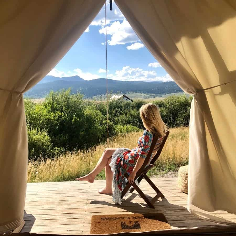 A woman sits on a wooden tent platform looking at the view at Under Canvas Yellowstone