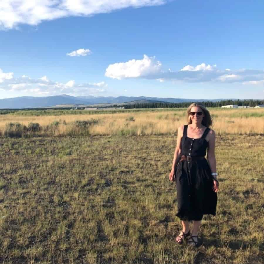 A woman walks in a field at Under Canvas Yellowstone