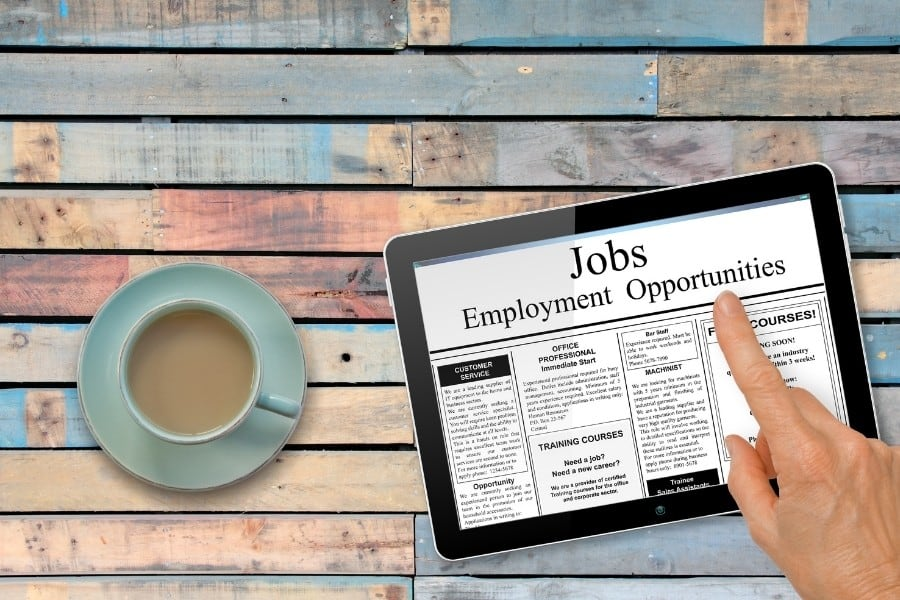 A tablet with someone looking at employment ads, sits next to a cup of coffee