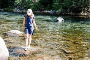 Susan Heinrich stands on a rock in a river in Beaver Creek Colorado
