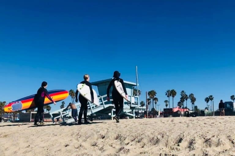 Three women surfers carry their boards on Venice Beach California