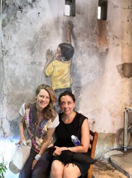 Two women sit on a chair underneath a mural titled Boy On A Chair in Penang