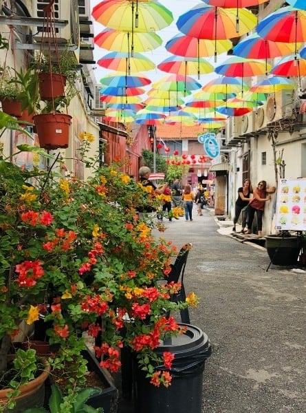 A colourful street with umbrellas at its top in Penang