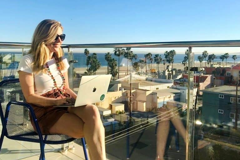 Susan Heinrich sits typing on a laptop and overlooking the Pacific Coast in L.A.