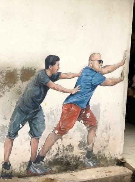 Two Men Pushing Door Mural in george Town Malaysia