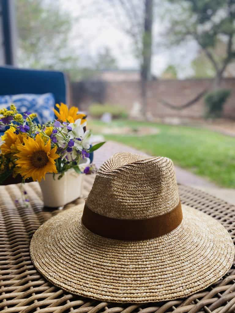 A straw fedora by Gigi Pip sits on an outdoor table next to a vase of wildflowers