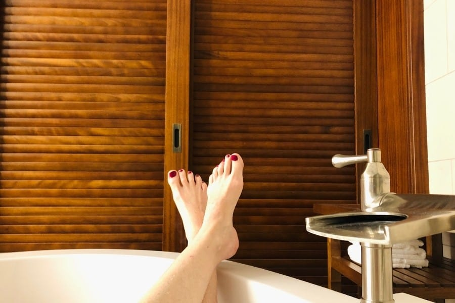 Feet rest in the side of a soaker tub at the Westin Nanea Ocean Villas