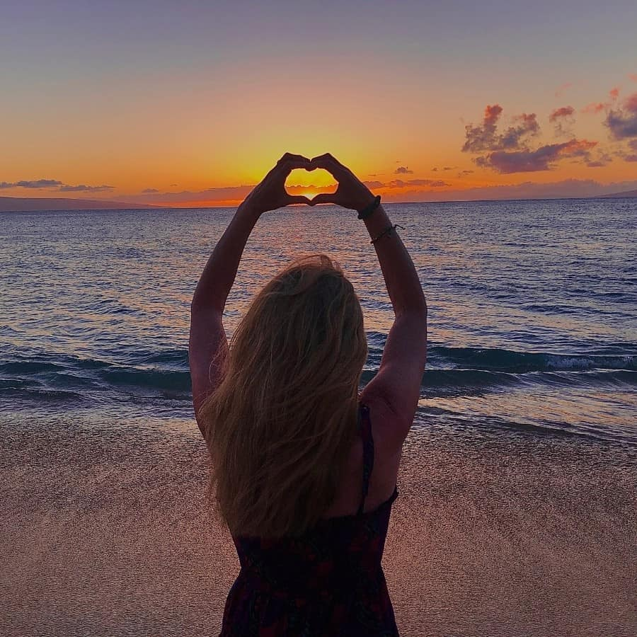 A woman holds up her hands to make a heart around the sunset at Kaanapali Beach in Maui