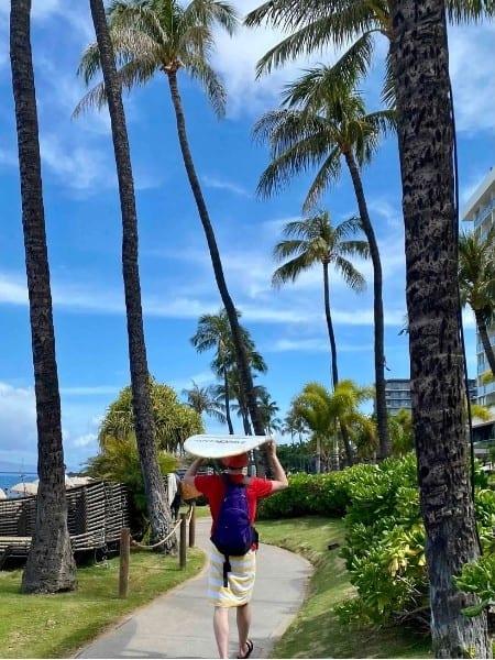 A man wlaks with a surfboard on his head at Kaanapali Beach Maui