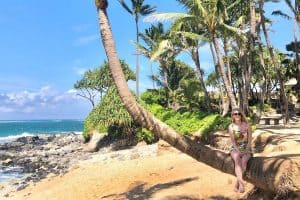 Susan Heinrich sits on a palm tree on a beach vacation in Maui