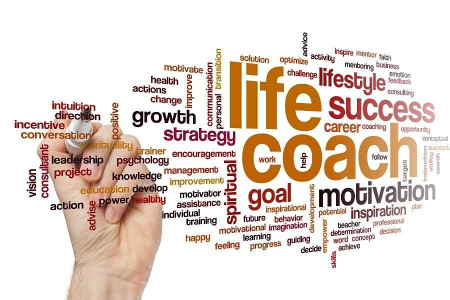 """A hand writes on a whiteboard with motivational words surrounding larger text that says """"life coach"""""""